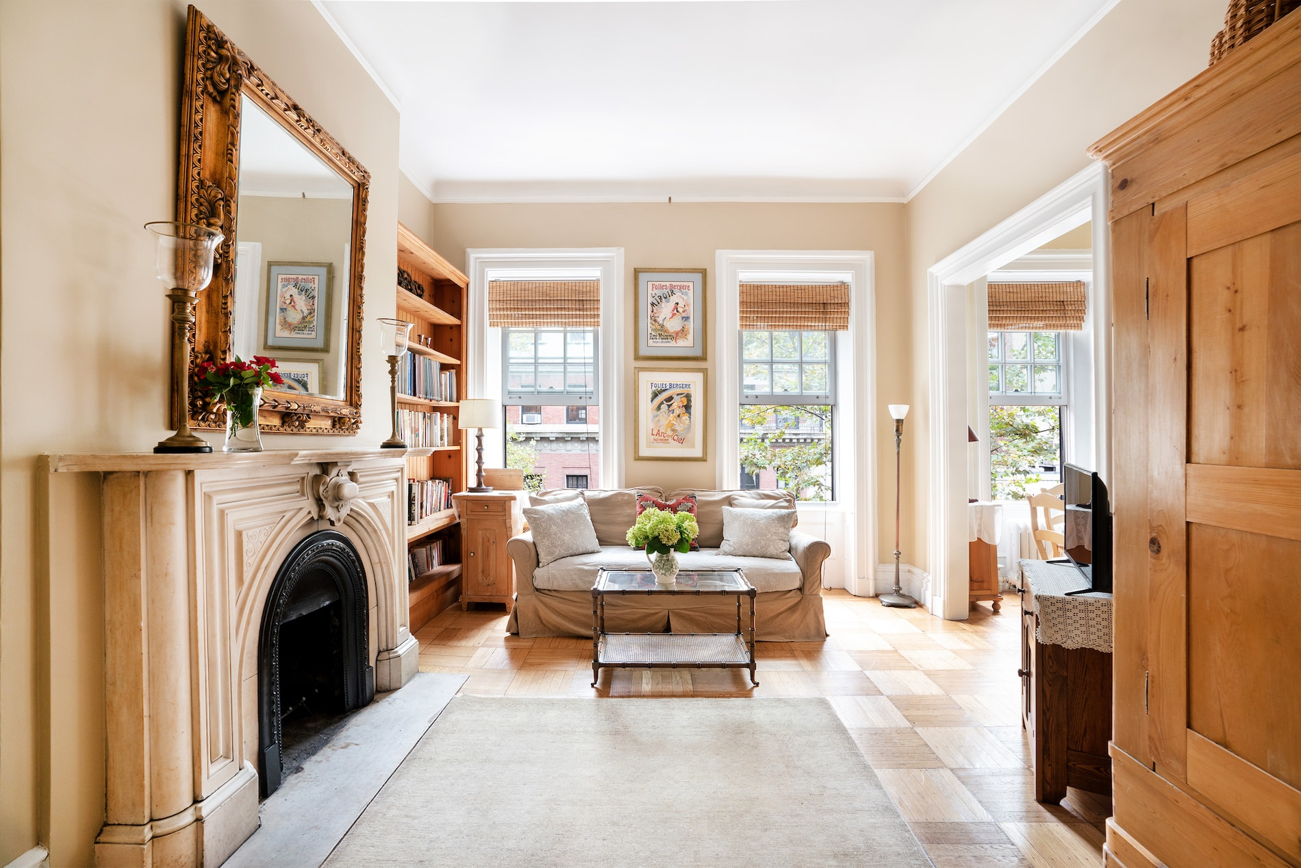 Well-lit sitting area with a tan & white sofa, glass coffee table, sitting chair, fireplace, bookshelves, & two tall windows