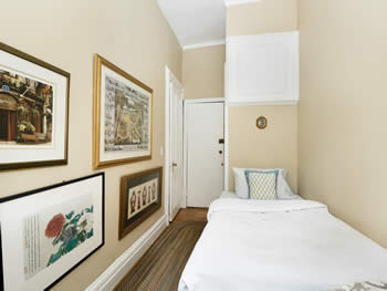 Eggshell-painted bedroom with a small white daybed, four hung artworks, & a hallway leading to two doors