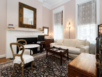 Parlor sitting area furnished with a cream sofa, wood coffee table, fireplace, & mini table with sitting chairs