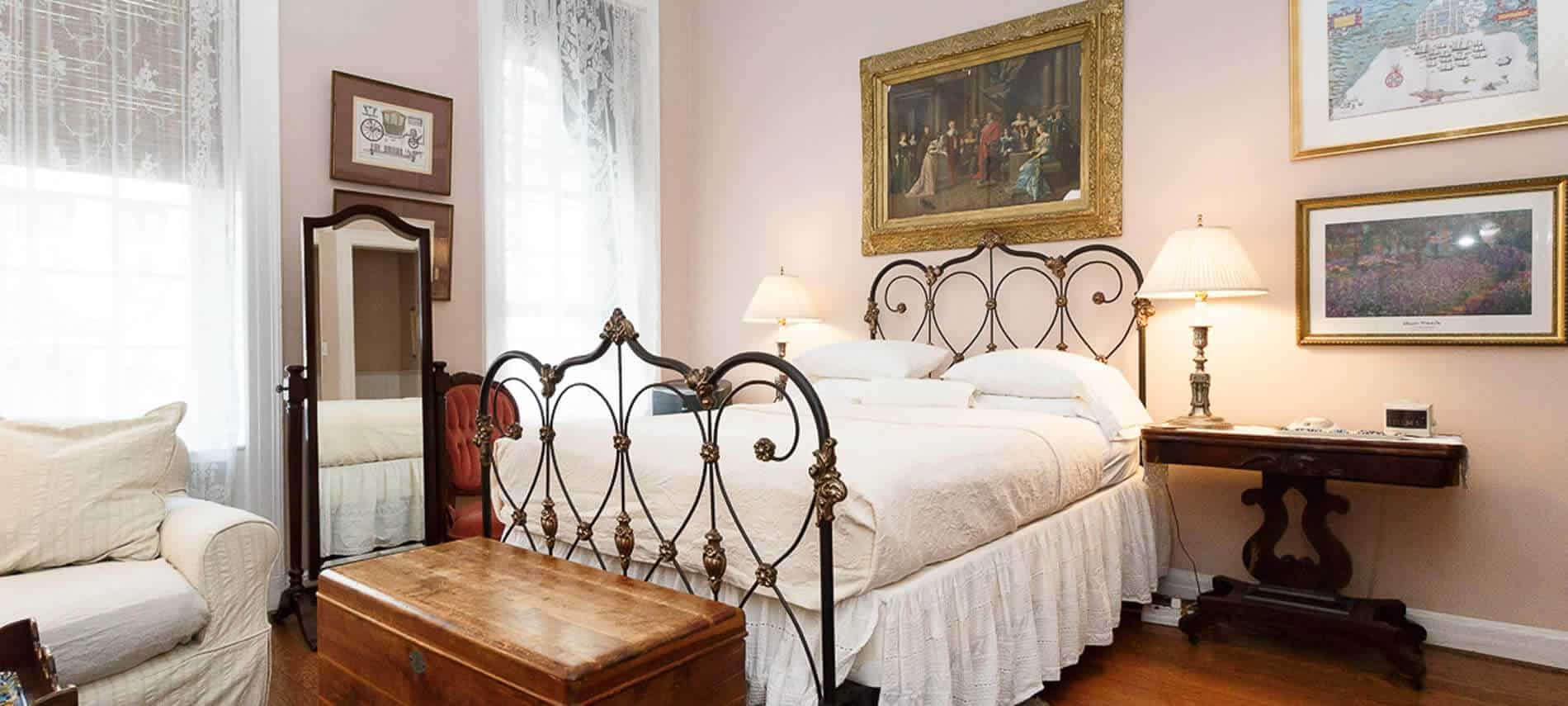 Bedroom furnished with a white & cream bed with a dark ornate bedframe, a standing mirror, two bedstands, & wooden chest