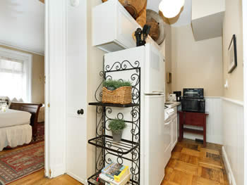 A bright kitchenette filled with white appliances, a black microwave, & a wire shelf unit with plants & books