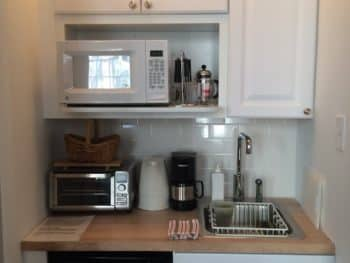 Small kitchen with white cabinets and light butcher block counter. Appliances are microwave, toaster oven, electric kettle and undercounter silver fridge.