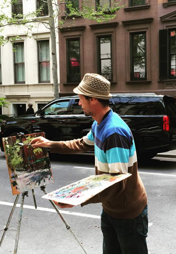 A male artist paints a New York City street on a small canvas outside the 1871 House Apartments