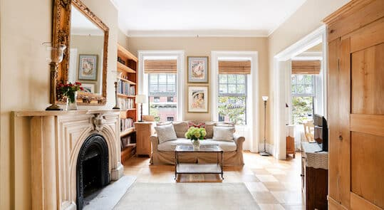 Brightly lit sitting area with a white & beige couch, a glass coffee table, a sitting chair, a fireplace, & two tall windows