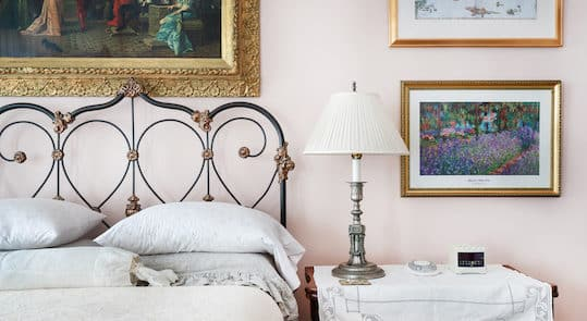 Bright bedroom furnished with a white-linen bed, wooden chest, white couch, & two bedstands with lamps