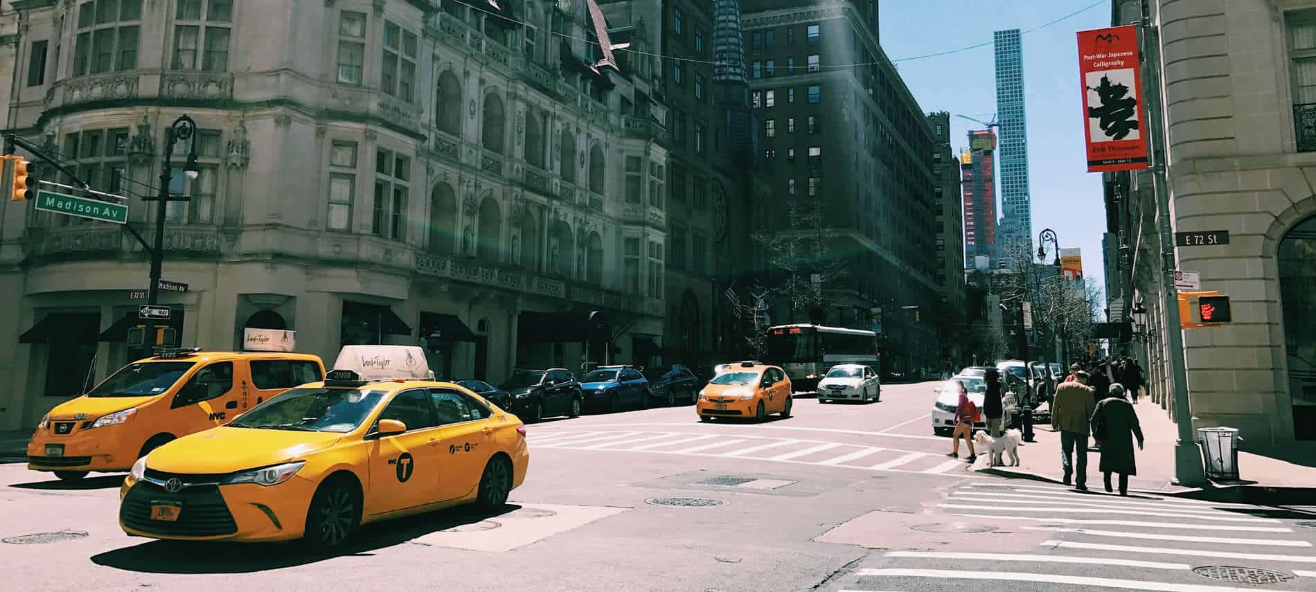 An intersection in New York City with multiple yellow taxis and crossing pedestrians during the day