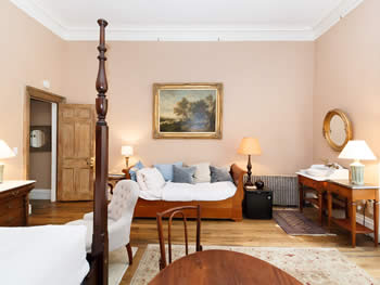 Pastel pink bedroom furnished with a tall poster bed, couch, table & chairs, & multiple side tables with lamps