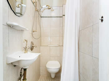 Cream-tiled bathroom with a white toilet, sink, & curtains, a gold & white shower head, & a mirror