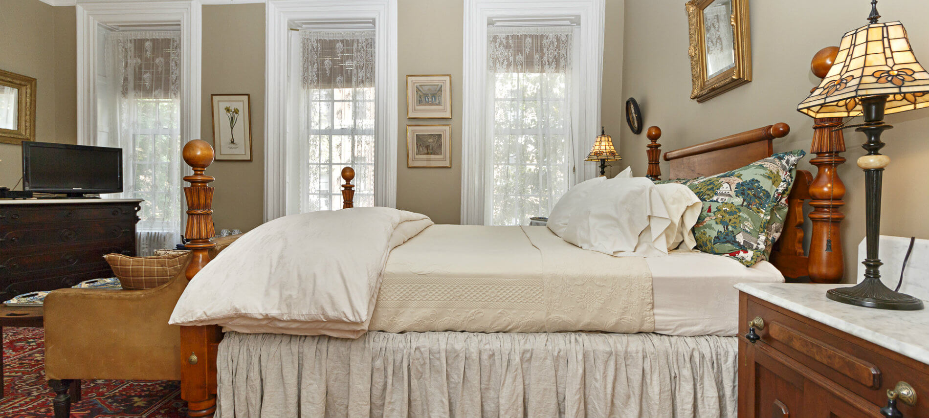 Soft beige walls with double large windows with white trim in room with large wood bed with soft cream linens and side table with small lamp