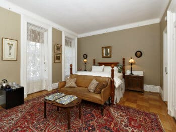 Beige-painted bedroom willed with a large poster bed, a tan leather couch, two bedstands, & a coffee table