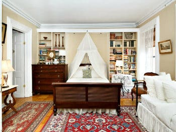 Bedroom furnished with a dark wood sleigh bed & white canopy, a white daybed, built-in bookshelves, & a wooden dresser