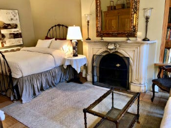 Eggshell-painted bedroom furnished with a large white bed, wooden wardrobe & tv stand, a bedstand, & a fireplace