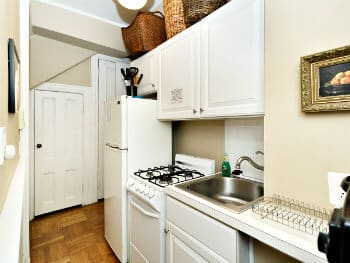 A bright kitchenette filled with white appliances, cooktop and storage