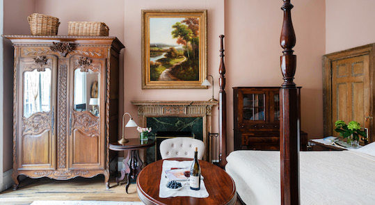 A well-lit room with pale rose-colored walls, a poster bed, wooden table & chairs, wardrobe, & a fireplace